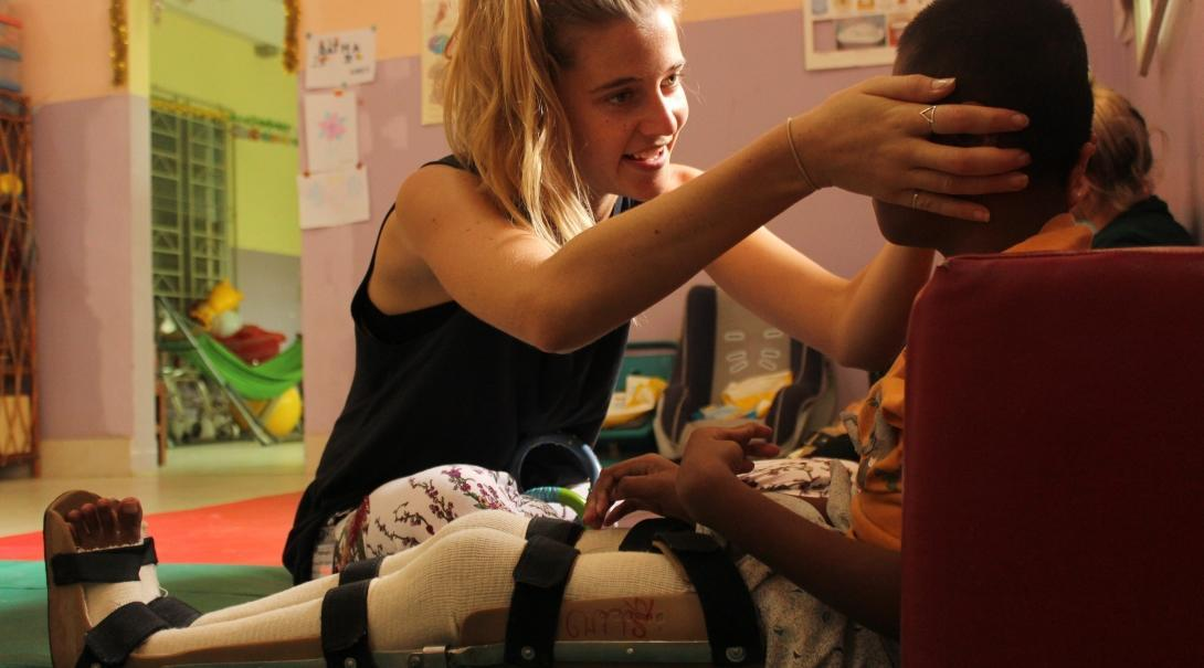 Projects Abroad intern helping a child as part of her physiotherapy internship in Cambodia.